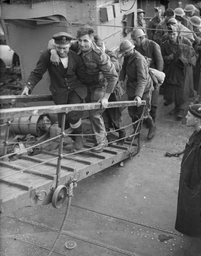 A merchant sailor assists a wounded british soldier up the gangplank from a destroyer Dover 31 May 1940